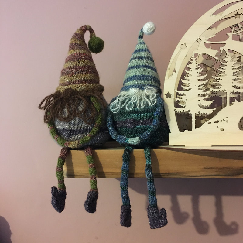 Two striped knitted gnomes sit on a shelf, with their legs dangling.