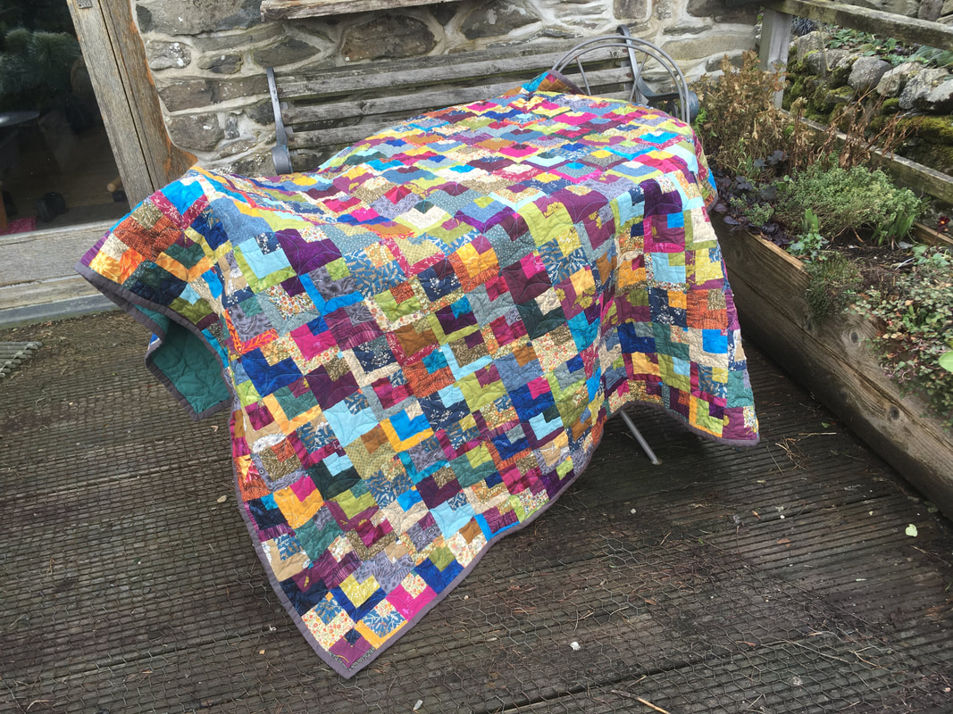 A multicoloured quilt draped over a table. The quilt is made from small squares of fabric, and in the top corner of each square is nested a smaller square, and within that an even smaller square.