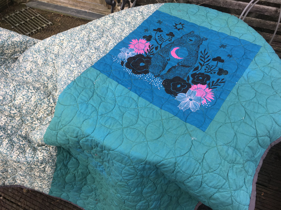 The back of the quilt, half is a white and green floral fabric, the other half plain sea-green, with an inset piece of teal fabric printed with a bear, surrounded by black and pink flowers.